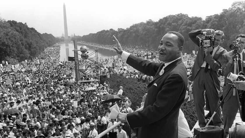 The Rev. Martin Luther King Jr. waves to supporters from the steps of the Lincoln Memorial during the March on Washington for Jobs and Freedom in 1963.