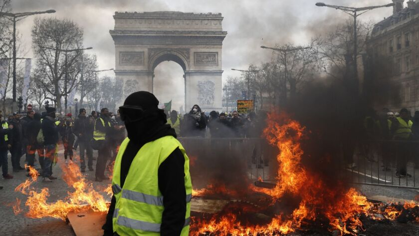 A yellow vest protester walks past a fire on the Champs Elysees avenue Saturday, March 16, 2019 in P