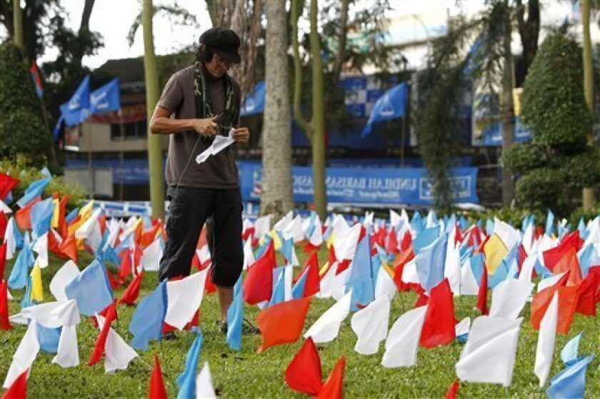 "In this Monday, April 22, 2013 photo, Malaysian landscape architect Ng Sek San, 50, prepares to plant miniature flags at a roundabout in Kuala Lumpur, Malaysia. Malaysians face a stark choice Sunday, May 5, 2013 in their most hotly contested general elections ever: Stick with what they know, a long-ruling coalition accused of corruption, or take a chance on an untested opposition. Ng has earned praise for his work in Malaysian hotels and parks, but he considers his latest initiative, the ""Malays"