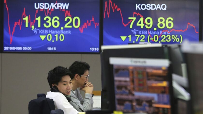 A currency trader talks on the phone at the foreign exchange dealing room of the KEB Hana Bank headquarters in Seoul on Friday.