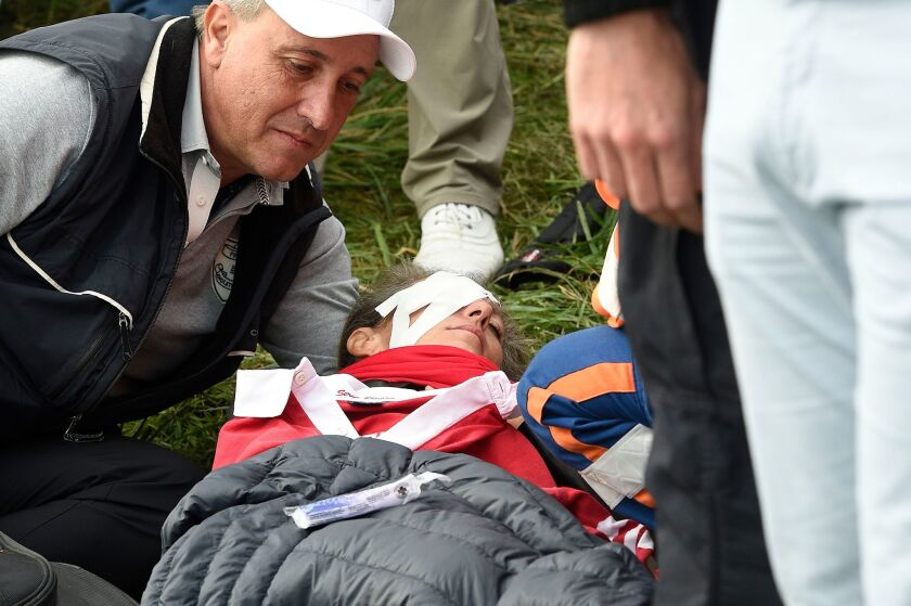 Corine Remande receives medical assistance after she was hit by Brooks Koepka's ball on the 6th hole during the Ryder Cup.