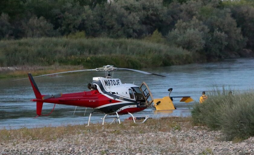A yellow, two-seat helicopter crashed into the Colorado River Saturday evening, Oct. 4, 2014 not far from the Loma exit off Interstate 70. A witness confirmed two fatalities as a result of the crash. Due to the remote nature of the accident scene, another helicopter was called into service to ferry personnel back and forth from the crash site. (AP Photo/Grand Junction Daily Sentinel, Christopher Tomlison)