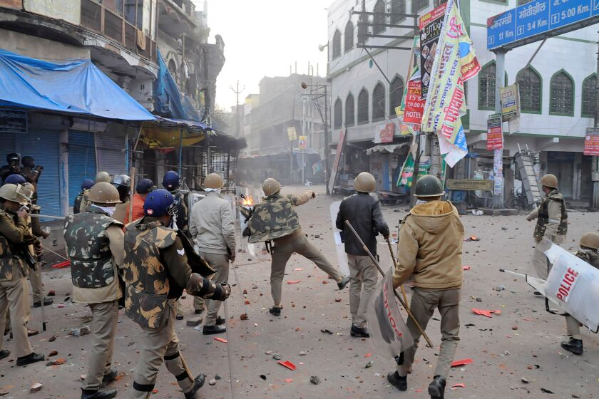 A police officer throws stones toward protesters in Kanpur during demonstrations against India's new citizenship law on Dec. 21.