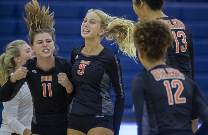 Huntington Beach's Hannah Ledesma (11), Claire Robbins (9), Olivia Carlton (13) and Xolani Hodel (12) celebrate winning a point in Game 5 of a nonleague match at Beckman on Wednesday.