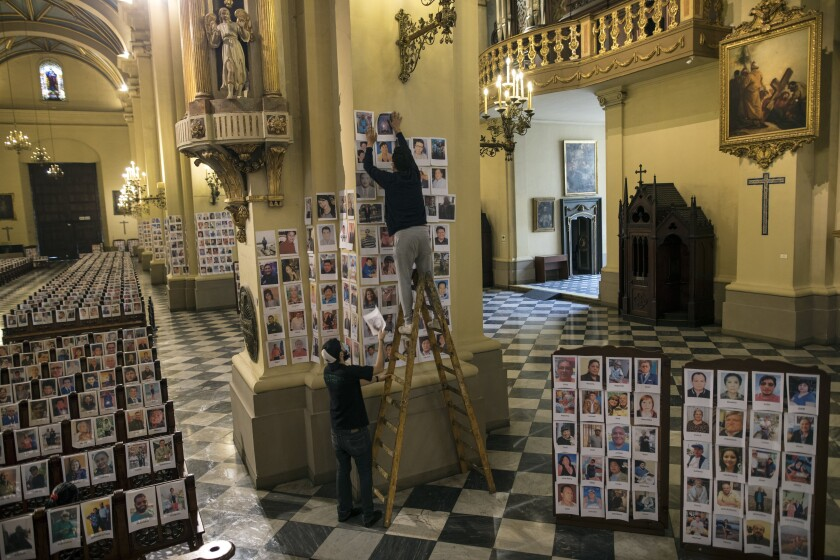 Workers stick portraits of people who died due to the COVID-19, inside the Cathedral, in Lima, Peru, Saturday, June 13, 2020. Sunday's mass in Lima's cathedral with the presence of more than 4,000 portraits of the dead from COVID-19 is the first with these characteristics in the South American country where until Saturday more than 6,400 had died and more than 225,000 were infected. (AP Photo/Rodrigo Abd)