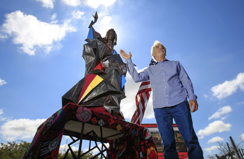 "San Diego Artist Jim Bliesner stands by a steel model of his statue titled ""Welcome Stranger""."