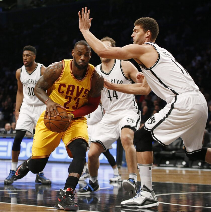 Brooklyn Nets center Brook Lopez (11) defends Cleveland Cavaliers forward LeBron James (23) who drives to the basket in the paint in the first half of an NBA basketball game, Thursday, March 24, 2016, in New York. (AP Photo/Kathy Willens)