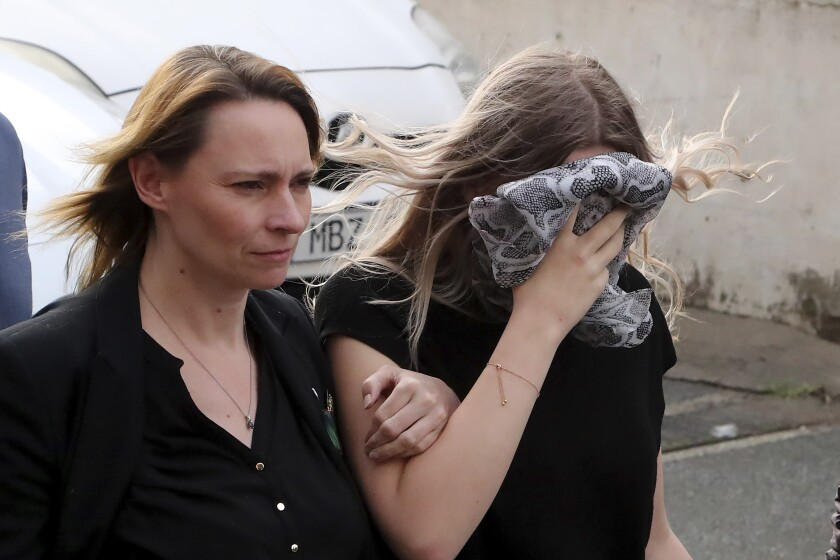 A 19 year-old British woman, right, that was found guilty of making up claims she was raped by up to 12 Israelis, arrives at Famagusta District Court with her mother for sentencing on Tuesday, Jan. 7, 2020. A Cyprus court handed a four-month suspended sentence to a 19-year-old British woman who was found guilty of public mischief for making up claims that she was raped by up to a dozen Israelis. (AP Photo/Petros Karadjias)