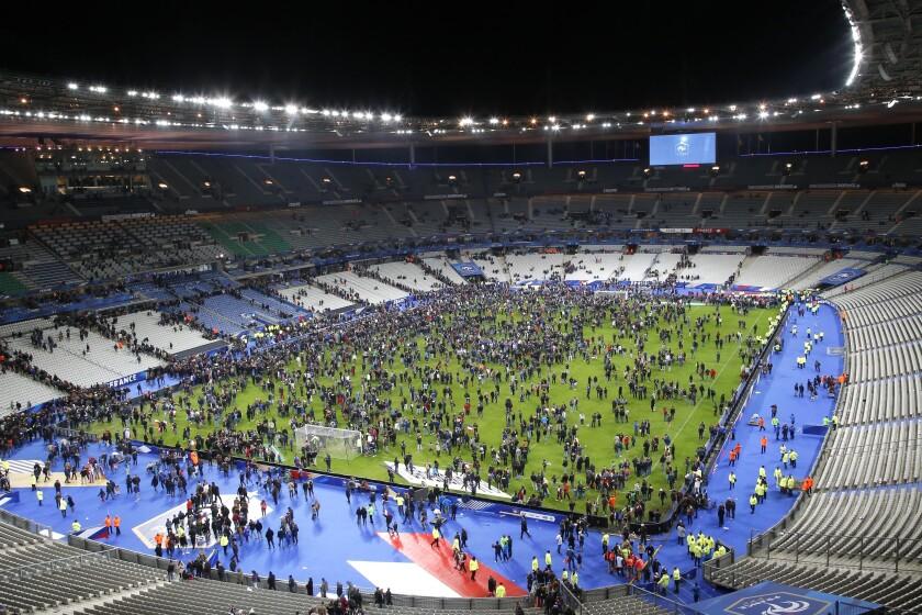 ARCHIVO - En esta foto del 13 de noviembre del 2015, espectadores invaden la cancha en el estadio Stade de France tras concluir un partido amistoso entre Francia y Alemania en Saint Denis, en las afueras de París. Víctimas de los ataques terroristas del 2015 en París comenzaron a declarar el 28 de septiembre del 2021 sobre la noche que dejó 130 muertos y decenas de heridos y las secuelas que ha dejado en los primeros testigos de la masacre. El testimonio comenzó con los policías montados que vieron a los dos primeros atacantes suicidas en el estadio nacional de fútbol. Los gendarmes, que eran 13 e n el sitio esa noche, estaban trabajando en control de muchedumbres en las afueras del estadio para el partido Francia-Alemania y absorbieron las ondas expansivas de las explosiones. (AP Foto/Michel Euler)