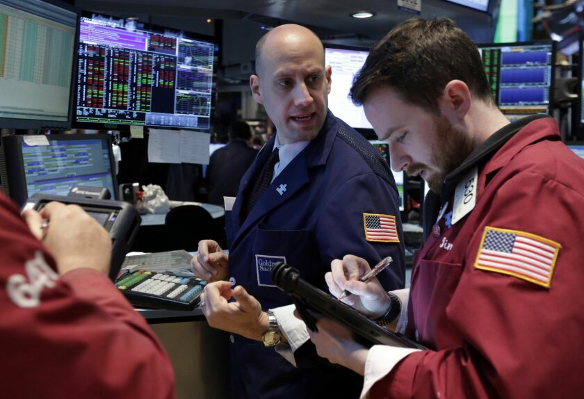 Specialist Meric Greenbaum, center, works at his post on the floor of the New York Stock Exchange Wednesday, April 30, 2014.  The stock market is edging lower Wednesday after the U.S. economy slowed more drastically in the first quarter than economists had believed. (AP Photo)