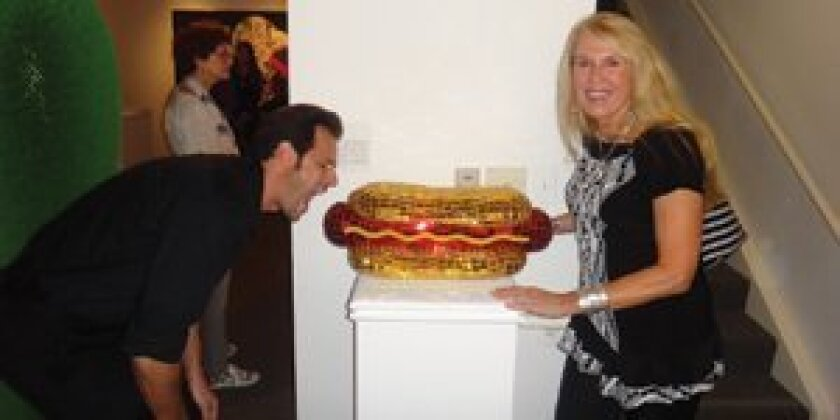 "Local artist Jean Wells' hot dog is currently on display in the Frederick R. Weisman Museum of Art's ""Pop Culture"" exhibit. She is seen here with fellow artist Robert Townsend pretending to take a bite."