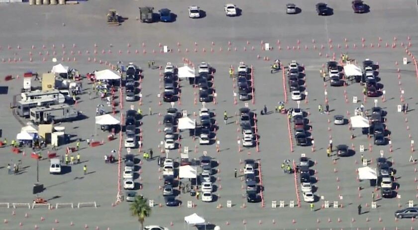 An aerial view of cars in a parking lot alongside tents and trailers.