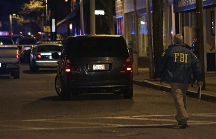 An FBI official arrives at the Watertown neighborhood of Boston, Friday, April 19, 2013. Reports of explosives being detonated and police are telling reporters to turn off their cell phones. Dozens of officers and National Guard members are in Watertown, where television outlets report that gunfire