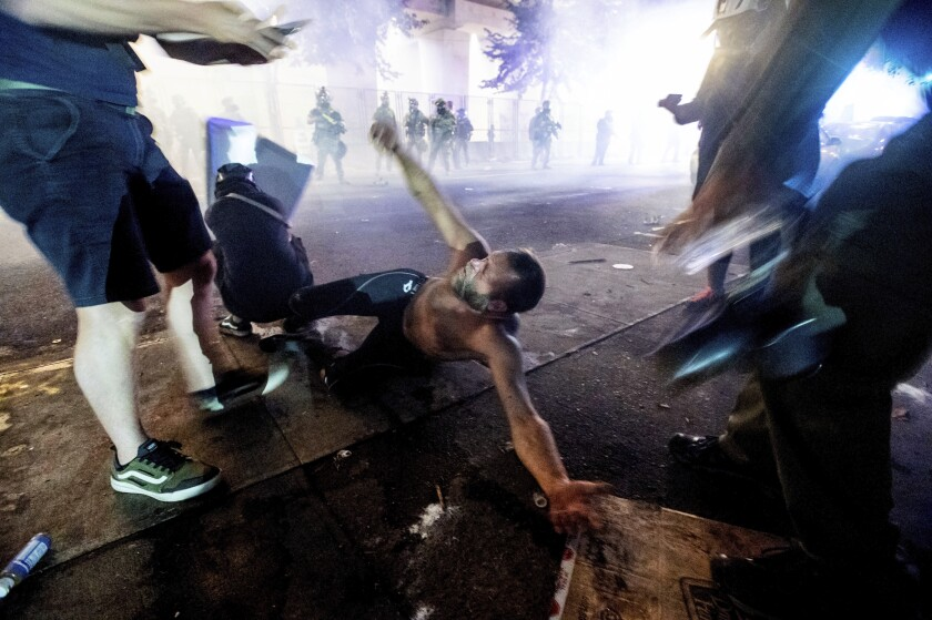A protester lies on the ground as federal officers use chemical irritants to disperse demonstrators in Portland, Ore.