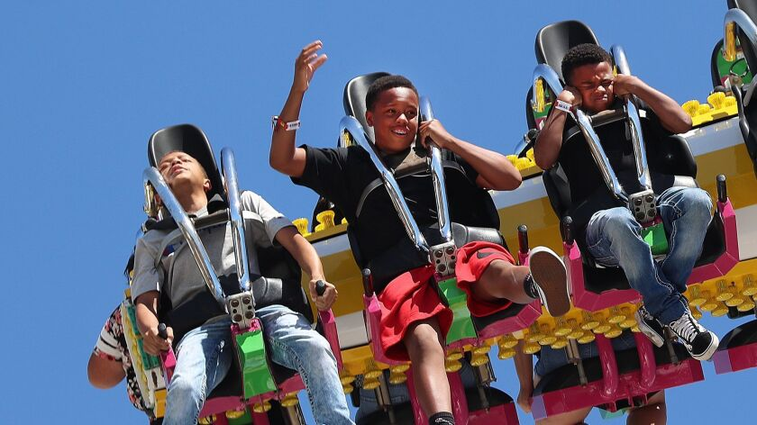 Kids have mixed reactions as they are sent upside down and sideways several times on the Tango ride on the first day of the Los Angeles County Fair on Aug. 31. Entrance prices won't increase this year, an effort to boost attendance.
