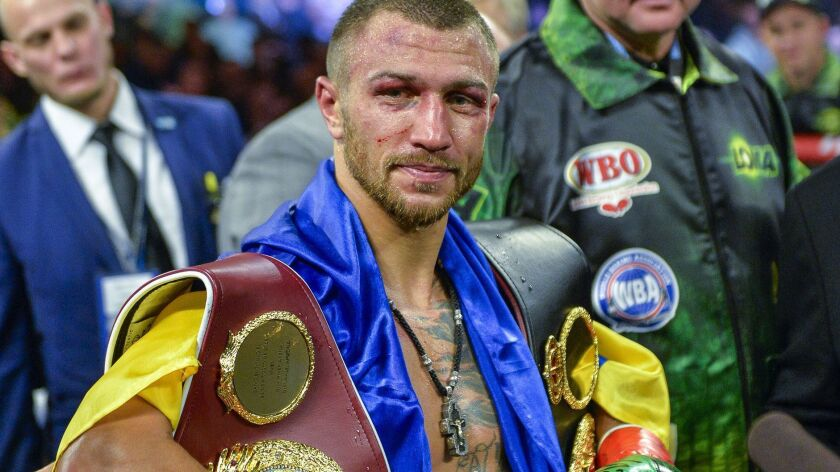 Vasiliy Lomachenko poses with the belts after defeating Jose Pedraza in the WBO title lightweight boxing match at Madison Square Garden on Dec. 8, 2018 in New York.