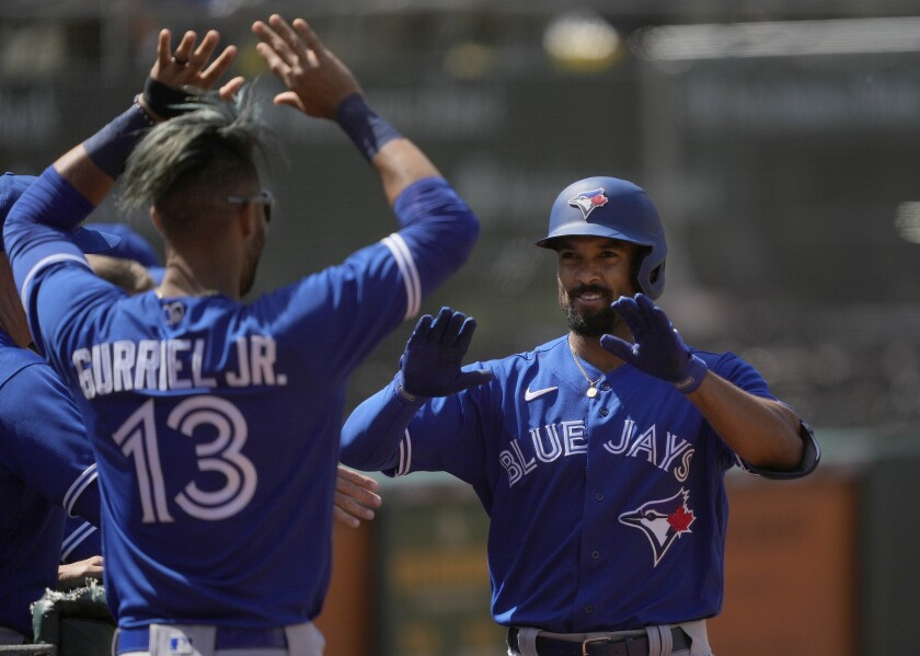 Toronto Blue Jays' Marcus Semien, right, celebrates with Lourdes Gurriel Jr. (13) after hitting a solo home run against the Oakland Athletics during the seventh inning of a baseball game in Oakland, Calif., Thursday, May 6, 2021. (AP Photo/Tony Avelar)