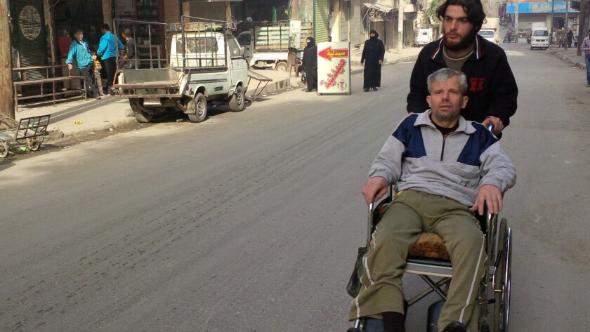 Abdullah Hawoot of the Hayat Medical Center wheels Mahmood, who is left paralyzed by a sniper's bullet, through the streets of Aleppo, Syria, after his therapy session.