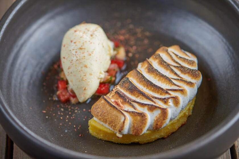 Elote Dulce at El Jardín Cantina is a delicious sweet corn pudding cake topped with a corn husk meringue, charred cob ice cream and a strawberry salsa.
