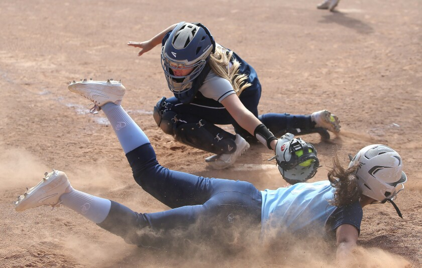 Newport Harbor catcher Kendall Kelly just misses the tag on Corona del Mar's Sydney Walls who scores during Battle of the Bay, Wave League softball game on Friday,
