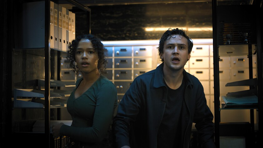 A young woman and man in a vault of safe deposit boxes looking scared