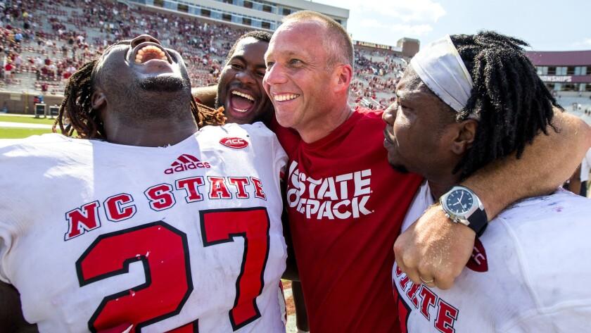 North Carolina State coach Dave Doeren celebrates with (from left) running back Dakwa Nichols (27),