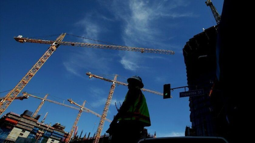 Construction cranes loom over a development site along Figueroa Street near L.A. Live in downtown Los Angeles.