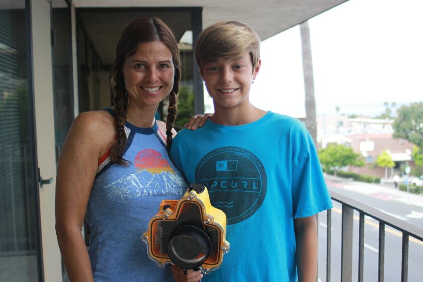 Aiden Rothschild with his camera in its waterproof housing, poses with mom, Laura.
