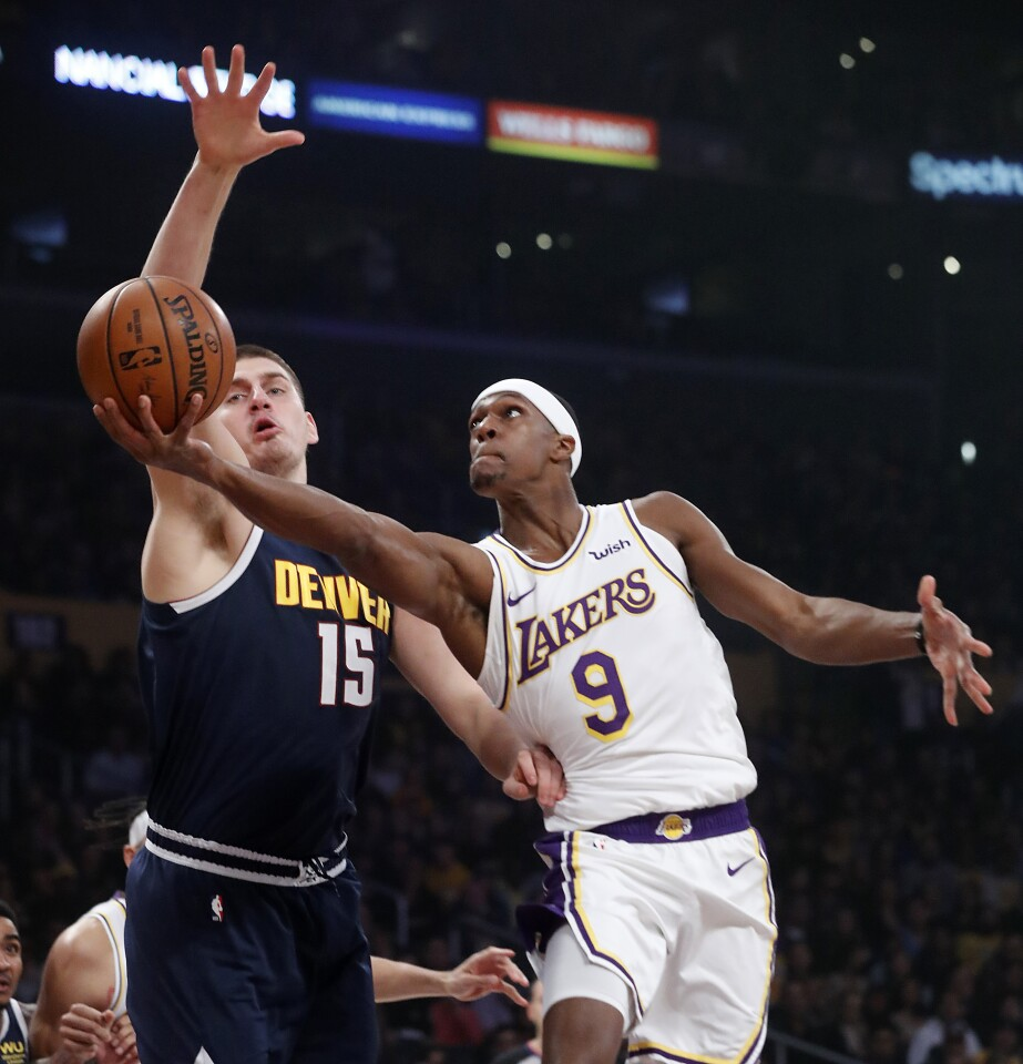 LOS ANGELES, CALIF. - DEC. 22, 2019. Lakers guard Rajon Rondo goes to the baket against Nuggets center Nikola Jokic in the first quarter Sunday night, Dec. 22, 2019, at Staples Center in Los Angeles (Luis Sinco/Los Angeles Times)
