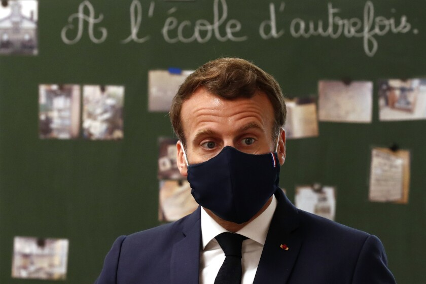 French President Emmanuel Macron, wearing a protective face mask, speaks in front of a blackboard at an elementary school