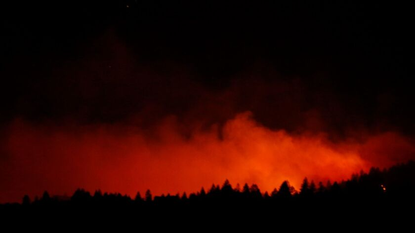 The Nuns fire crests over a line of trees as seen from Highway 29 north of Yountville on Oct. 13.
