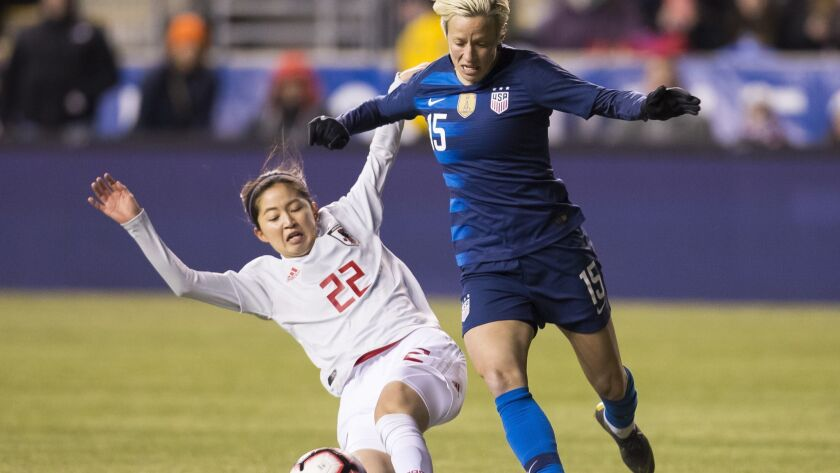 United States' Megan Rapinoe, right, tries to get around Japan's Risa Shimizu, left, with the ball d