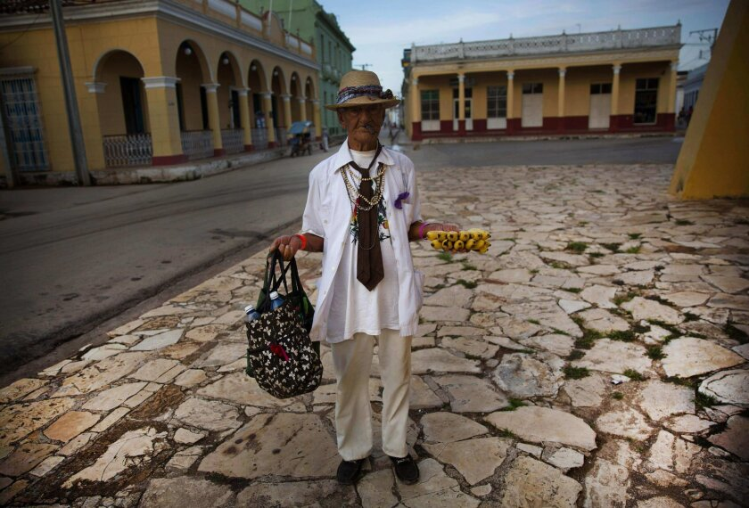 In this Sept. 1, 2016 photo, 90-year-old street vendor Antonio Bauza waits for tourists to sell bananas to, next to the village church in Remedios, Cuba. With the arrival of the first commercial flights from the U.S. to Cuba in more than 50 years, the Cuban government is welcoming the wave of new v