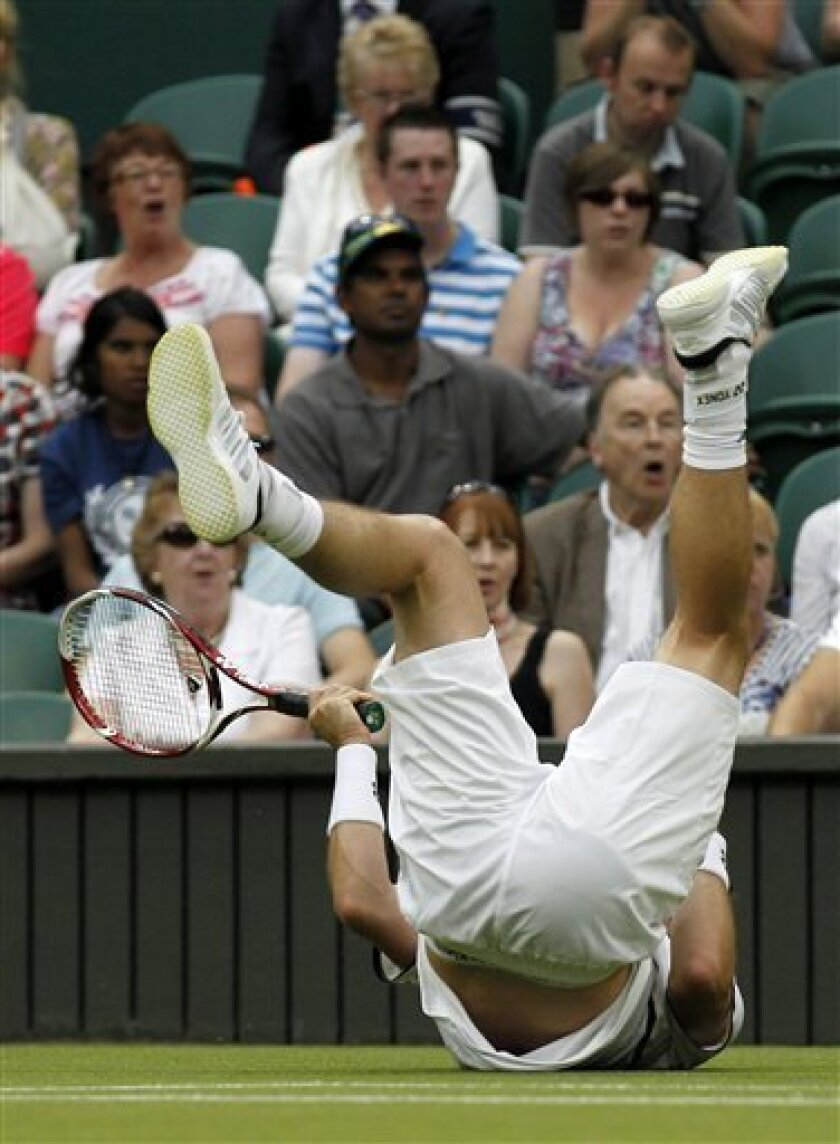 Australia's Lleyton Hewitt falls to the ground during the match against Sweden's Robin Soderling at the All England Lawn Tennis Championships at Wimbledon, Thursday, June 23, 2011. (AP Photo/Anja Niedringhaus)