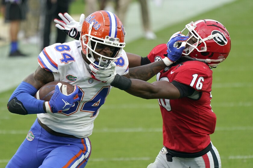 Florida tight end Kyle Pitts (84) tries to get past Georgia defensive back Lewis Cine (16) after a catch Nov. 7, 2020.