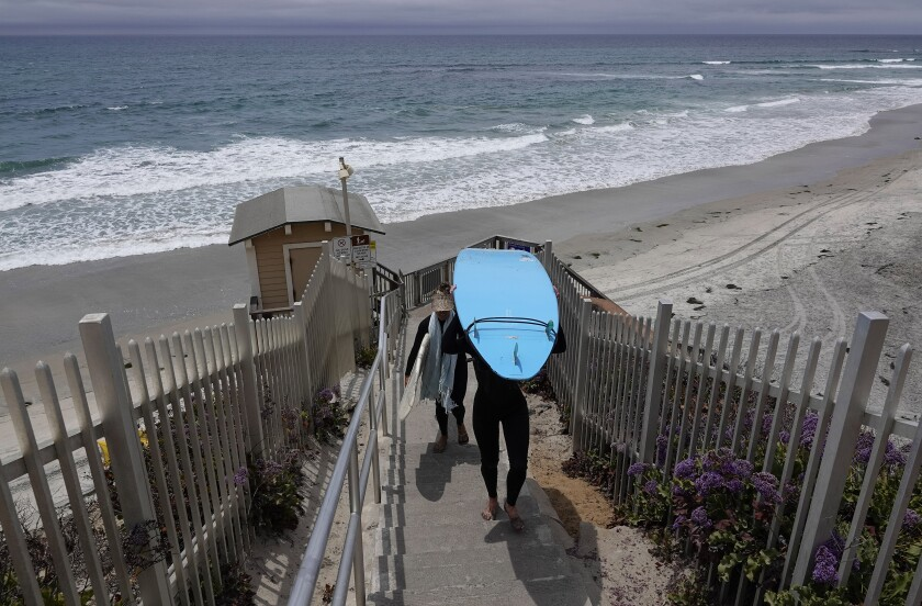 Surfers walk up the stairs at Tide Beach Park in Solana Beach on Tuesday, June 29, 2021.