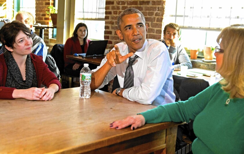 President Obama speaks about his push for paid leave for workers with Mary Stein, right, and Amanda Rothschild at Charmington's cafe in Baltimore.