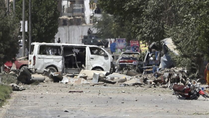 Destroyed vehicles, including a white van, sits at the site of an explosion in Kabul, Afghanistan, M
