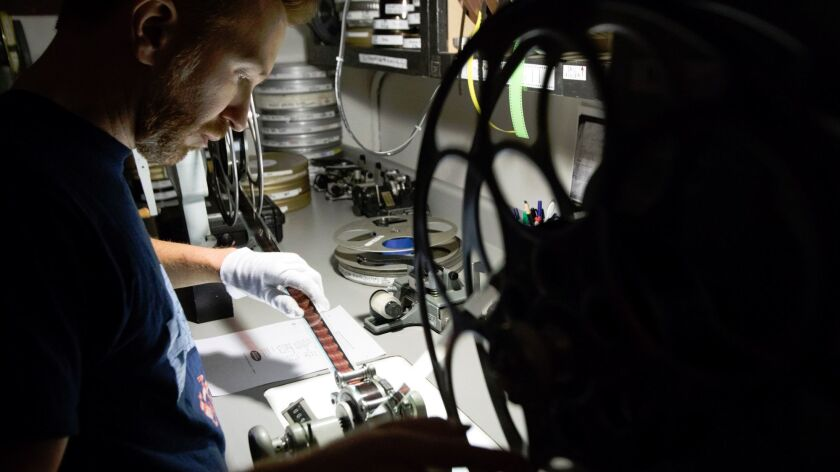 New Beverly Cinema archivist Aaron Martz inspects a film to make sure it's not damaged and is ready