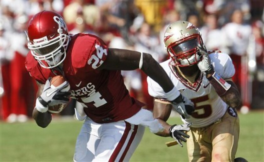 Oklahoma wide receiver Dejuan Miller, left, is chased by Florida State cornerback Greg Reid during the second quarter of an NCAA college football game in Norman, Okla., Saturday, Sept. 11, 2010. (AP Photo/Sue Ogrocki)