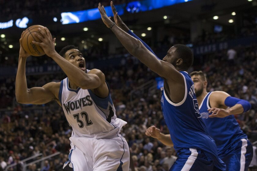 Minnesota Timberwolves centre Karl-Anthony Towns, left, turns to shoot on Toronto Raptors forward Patrick Patterson during the second half of an NBA basketball game in Toronto on Thursday, Dec. 8, 2016.