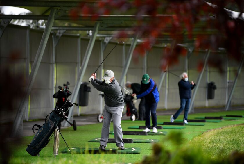 People in face masks practice at a traditional, one-level driving range