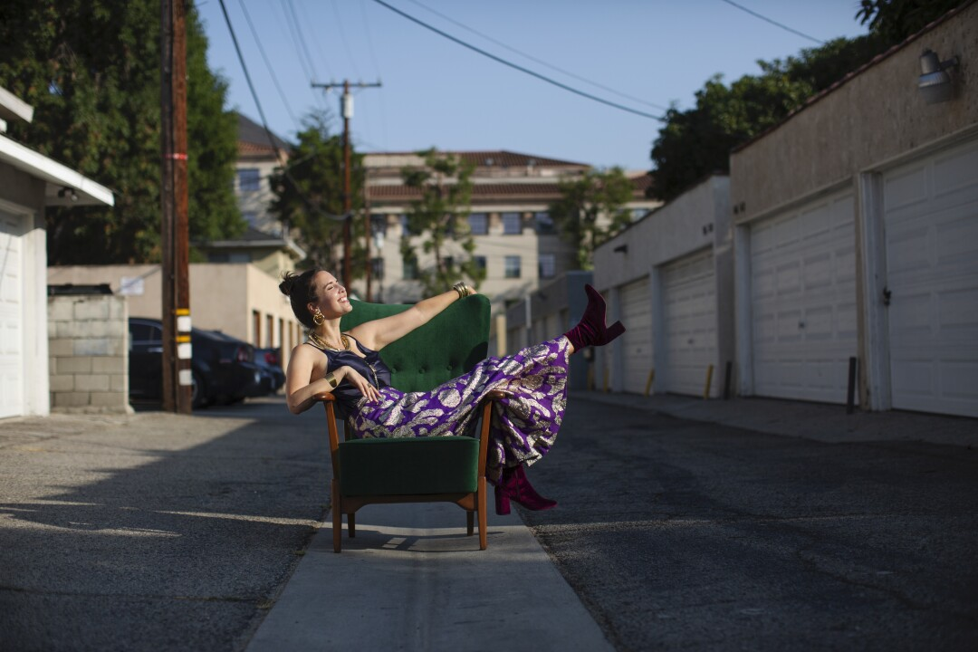 Analise McNeill poses in an alley on a green chair.