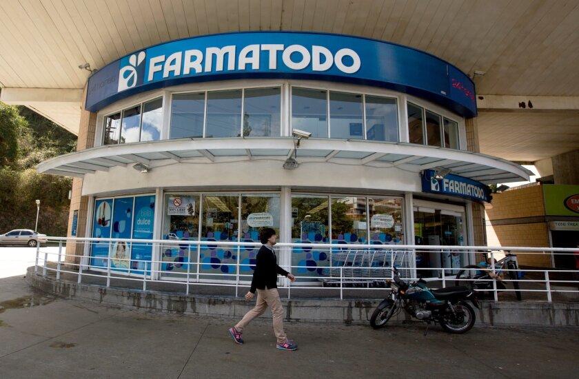 A pedestrian walks past a Farmatodo pharmacy in Caracas, Venezuela, on Monday.