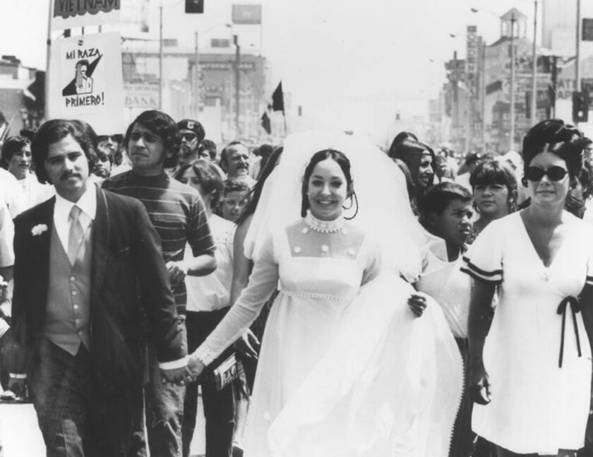 A newly wedded couple march in the National Chicano Moratorium in East Los Angeles on Aug. 29, 1970.