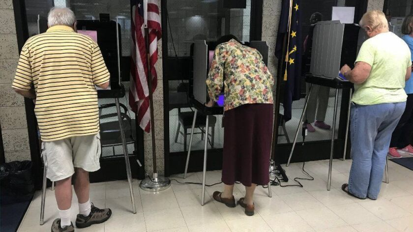 Early voters cast ballots Oct. 10, 2018, at the Lake County Government Center in Crown Point, Ind. Three companies sell and service more than 90 percent of the machines on which votes are cast and results tabulated. Experts say they skimp on security.
