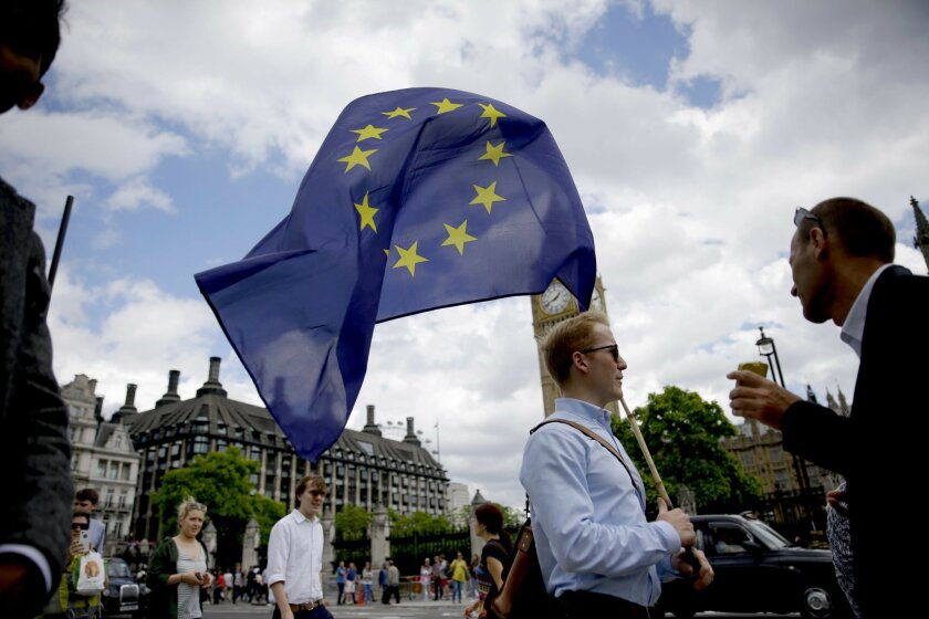 FILE - In this Friday, June 24, 2016 file photo, a remain supporter stops to talk to people as he walks around with his European flag across the street from the Houses of Parliament in London. (AP Photo/Matt Dunham, File)