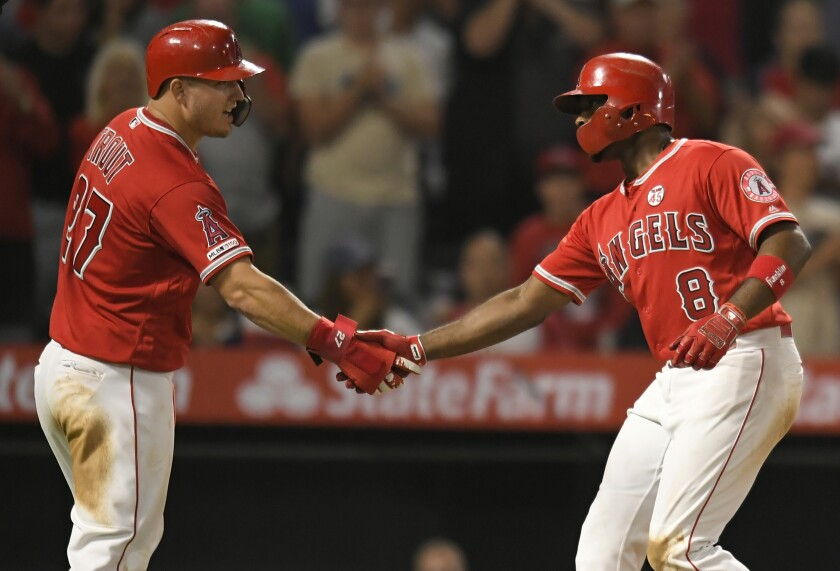 Angels' Mike Trout, left, congratulates Justin Upton after he hit a three-run home run in the sixth inning against the Chicago White Sox at Angel Stadium on Thursday.