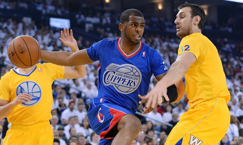 Clippers point guard Chris Paul, left, looks to pass around Golden State Warriors center Andrew Bogut during the Clippers' Christmas Day loss. Paul likely will not return from a separated shoulder injury until mid-February.