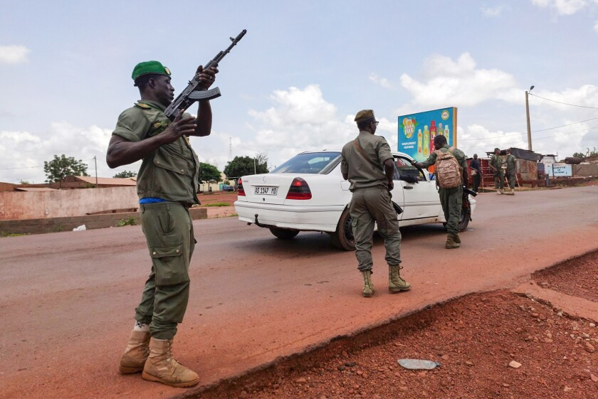 Malian soldiers check a vehicle in the garrison town of Kati, Mali.